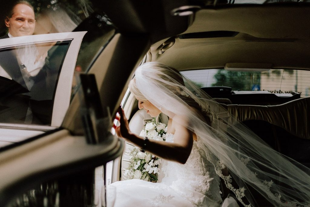 Bride-stepping-out-of-car-at-weddingday-wedding-videographer-still